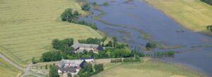 Flygbild över kringbyggda gårdar, åkrar samt ett översvämmat vattendrag.