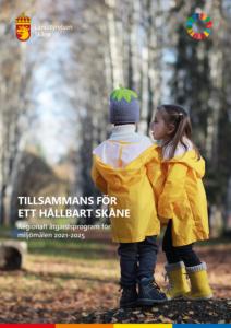 """Framsida till remissrapporten """"Tillsammans för ett hållbart Skåne. Regionalt åtgärdsprogram för miljömålen 2021-2025."""" På bilden syns två barn i gula regnjackor. I bakgrunden syns träd lite suddigt."""