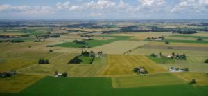 Flygfoto som visar skånska åkrar och gårdar som ett lapptäcke
